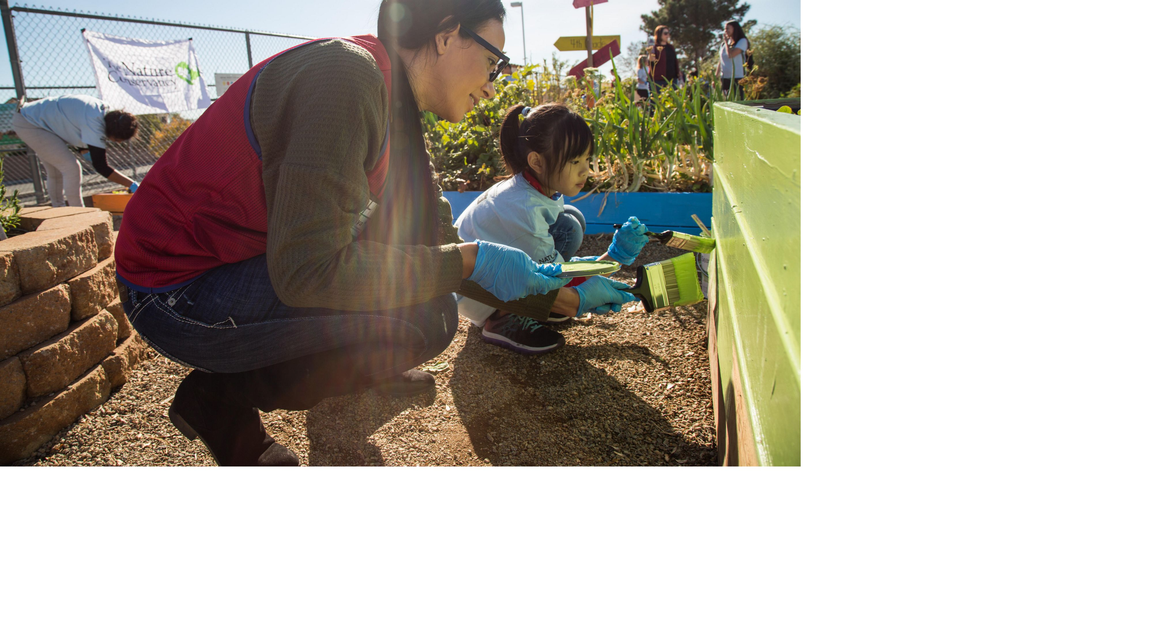 Students from Roger Bryan Elementary School and volunteers from Lowe's paint planter beds in Las Vegas, Nevada for a garden build volunteer day.