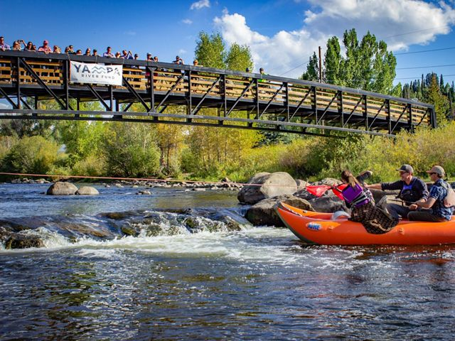 A boat of people cut a ribbon on the Yampa River.