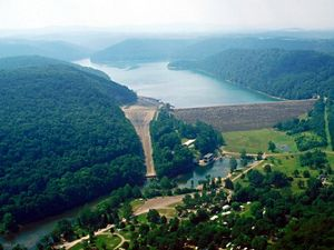 A dam is surrounded by green hills thick with trees.