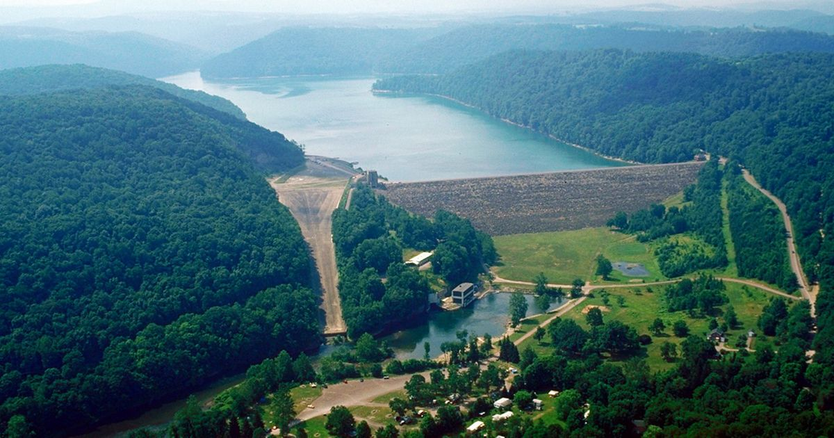 A dam is surrounded by hills blanketed in green trees.