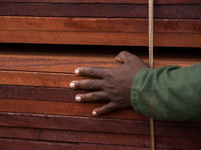 A hand on top of a stack of processed wooden planks