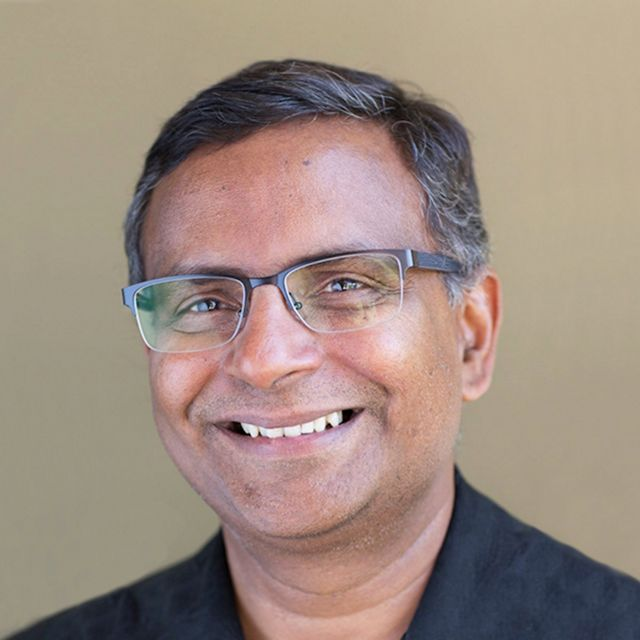 Headshot of smiling man with glasses.