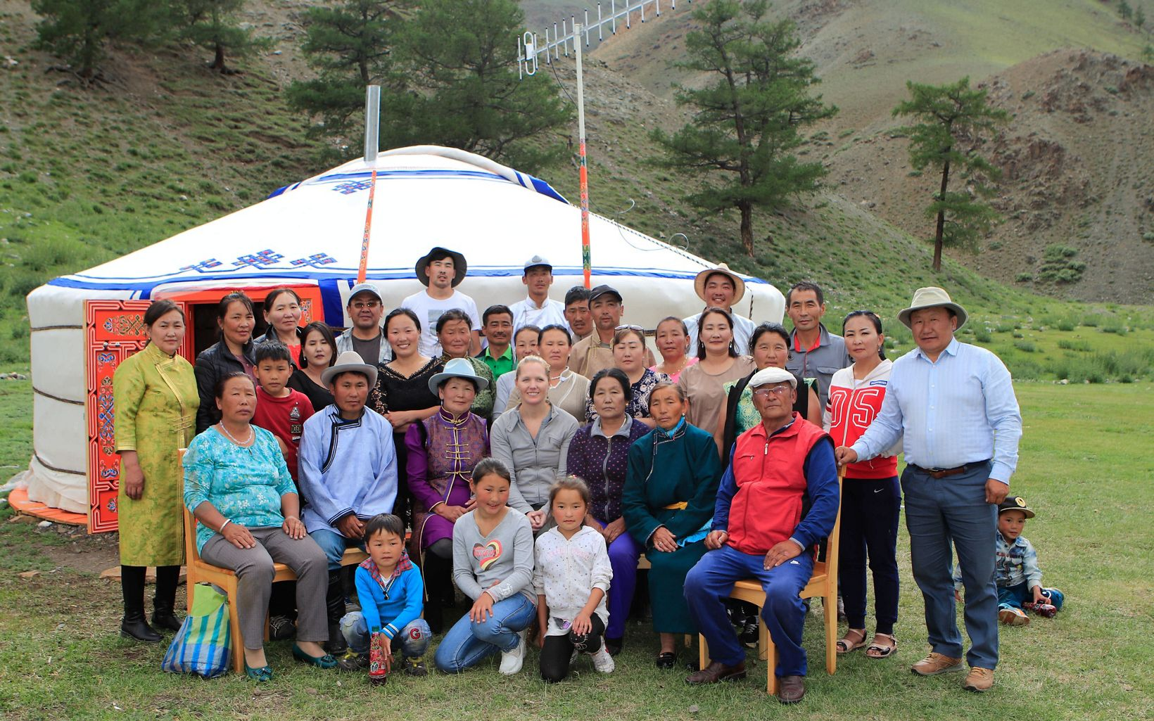 The local community poses in front a Mongolia ger tent at their eco-camp.