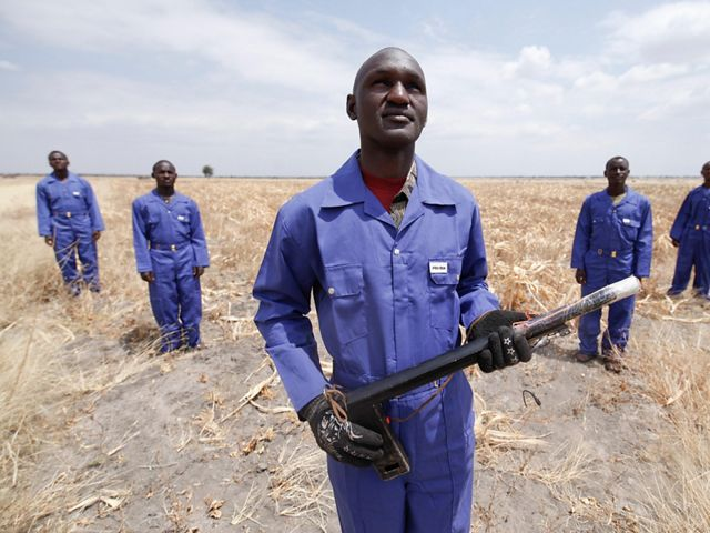 """Ombeni ISaya, a member of a crop protection team in Tanzania's Randilen WMA, holds a """"fire launch,"""" as part of the """"elephant alarm system."""""""
