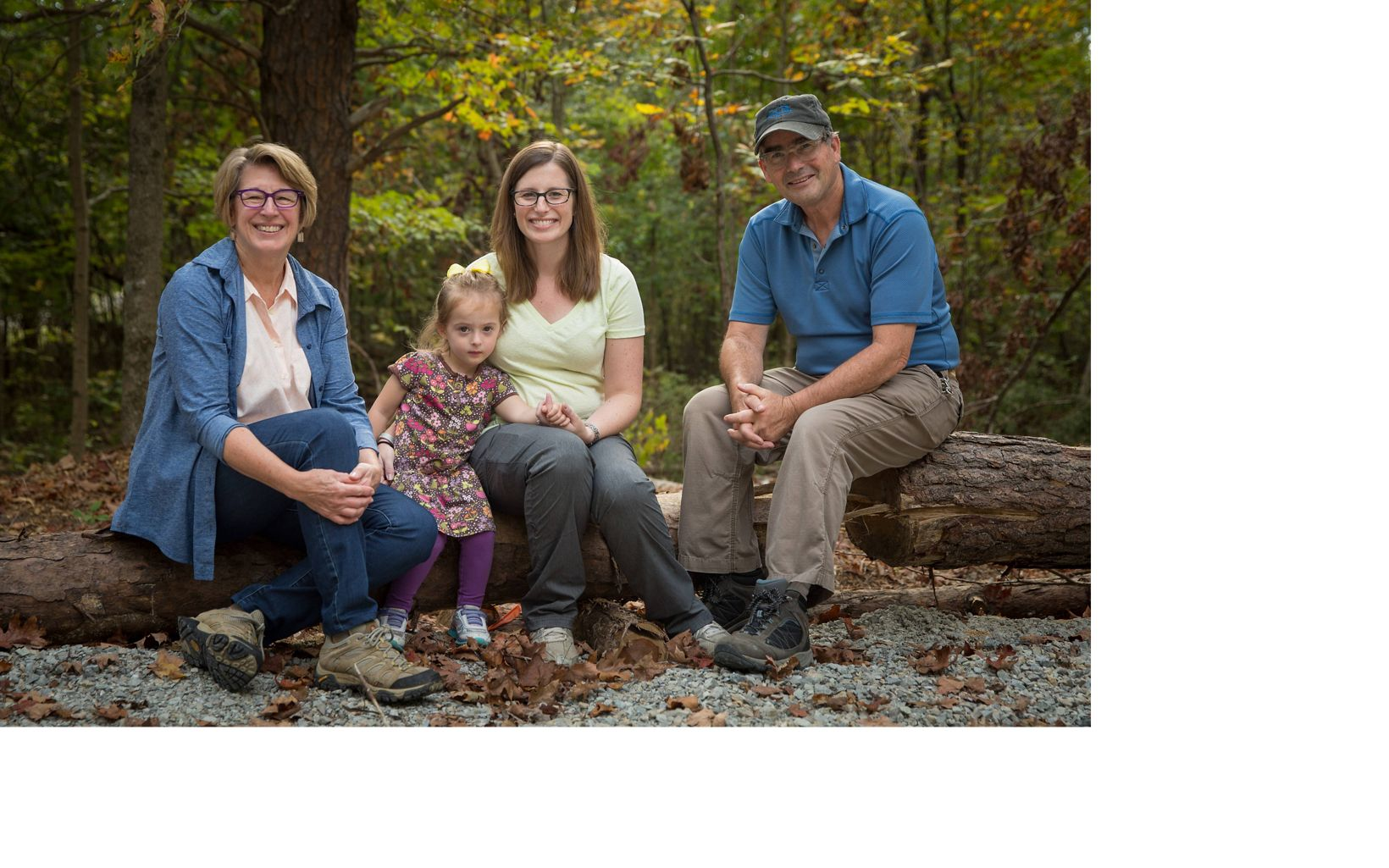 Three adults and a child pose on a log in the forest.