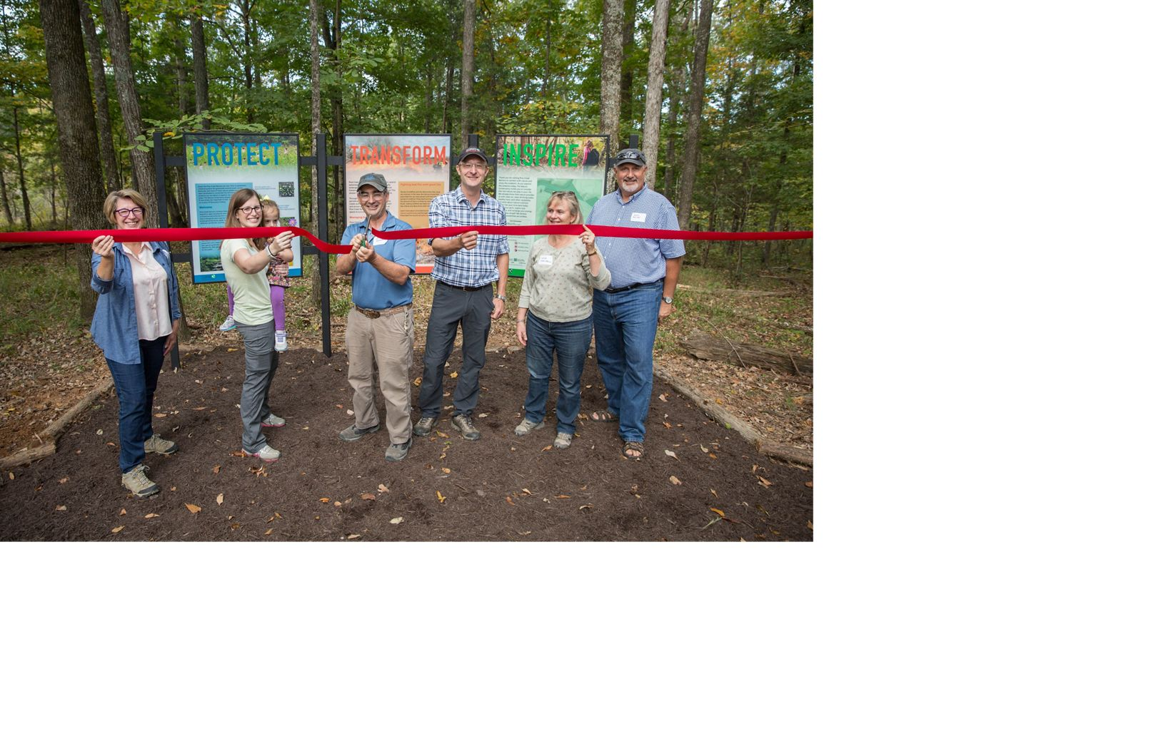 Six people line up to cut a red ribbon.
