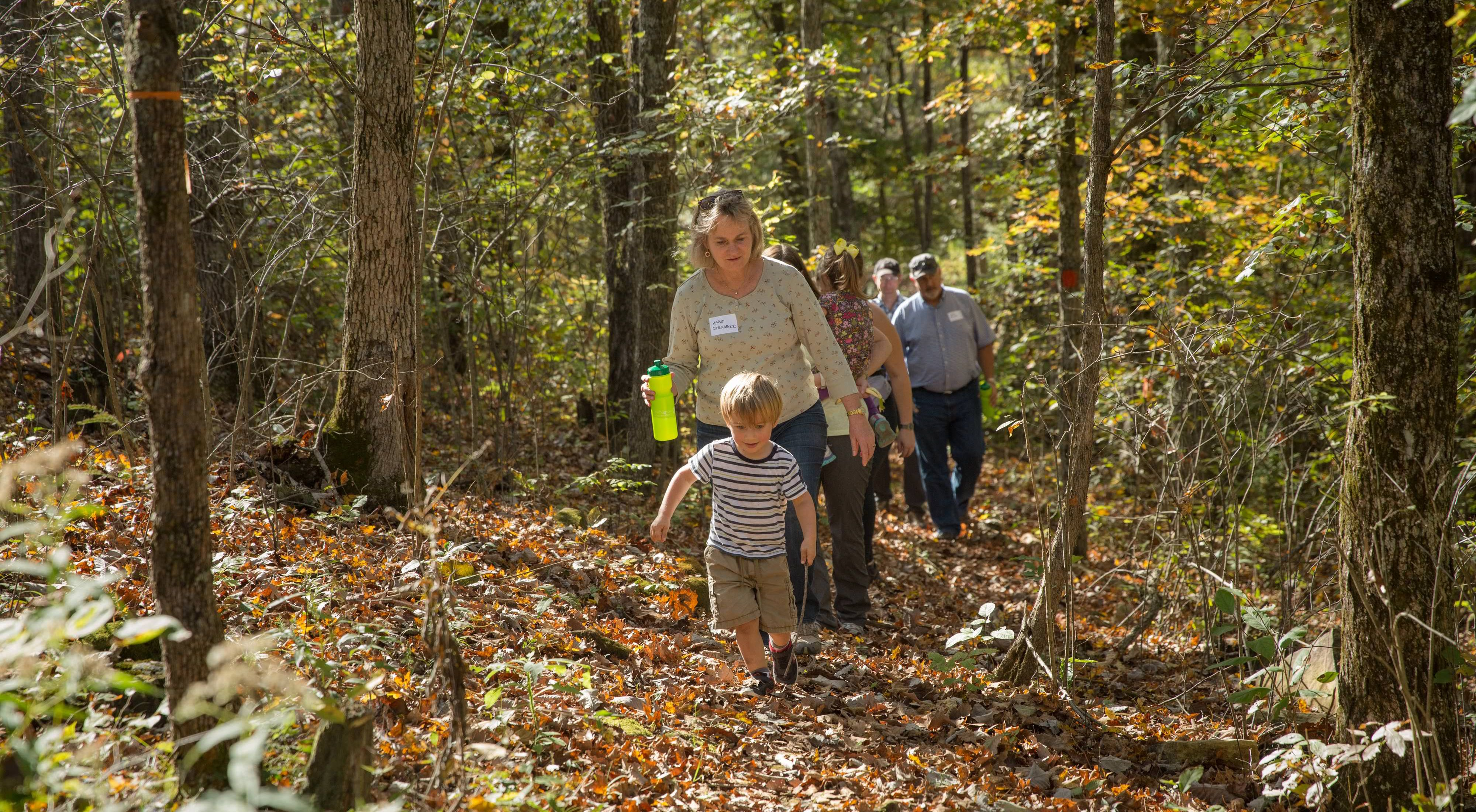 Led by a child, three people hike up a leafy trail surrounded by forest.