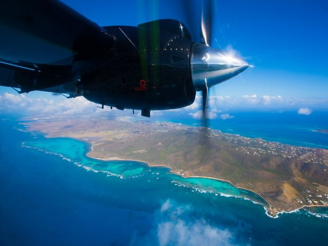 Island of St. Croix and blue ocean are seen below, with plane propeller of Global Airborne Observatory above