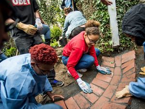 Volunteers laying pavers in an urban garden