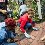 Youths place bricks at a new urban park.