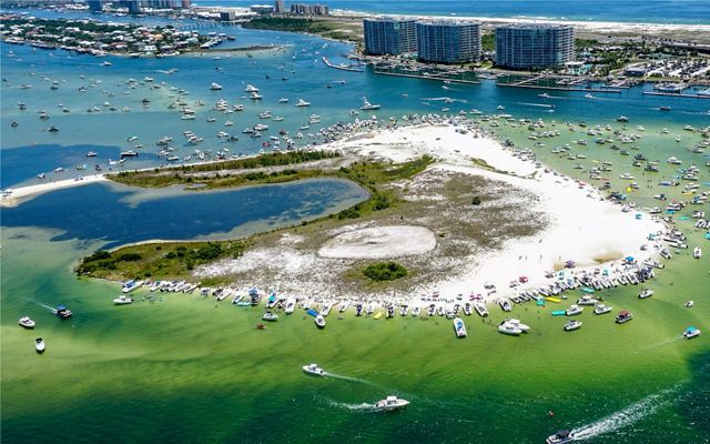 An aerial view of a sandy island densely surrounded by boats, with marinas and high rise buildings in the distance.