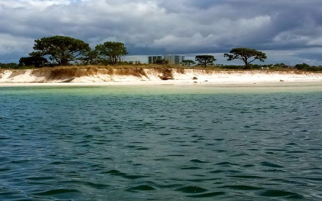 An eroding white sand beach seen from the water.