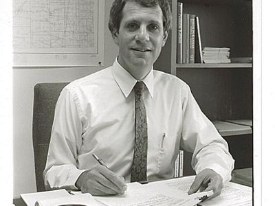 Alan Pollom sitting at desk holding papers