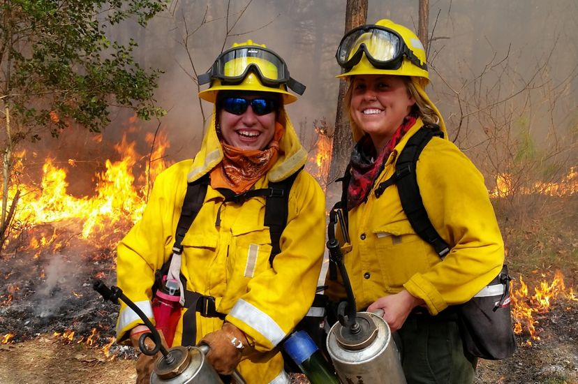 Two women wearing yellow fire retardant gear pose together during a controlled burn. They are both holding silver drip torch canisters. A line of fire burns behind them as smoke rises around them.