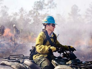 Woman riding on 4-wheeler through controlled burn.