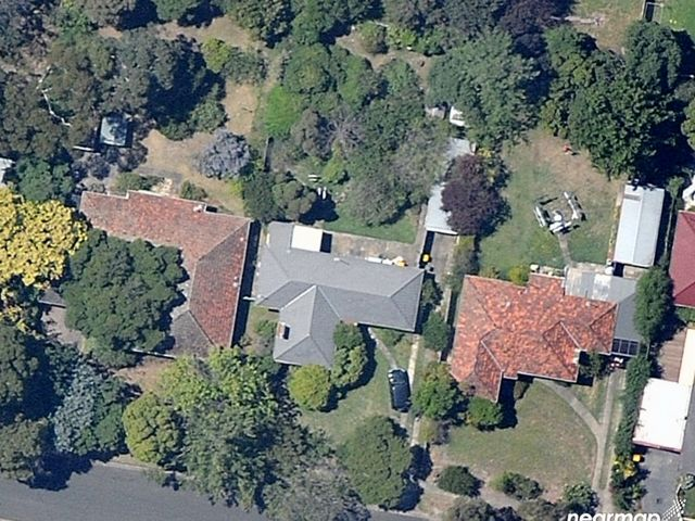 An aerial view of 3 houses surrounded by tree canopy