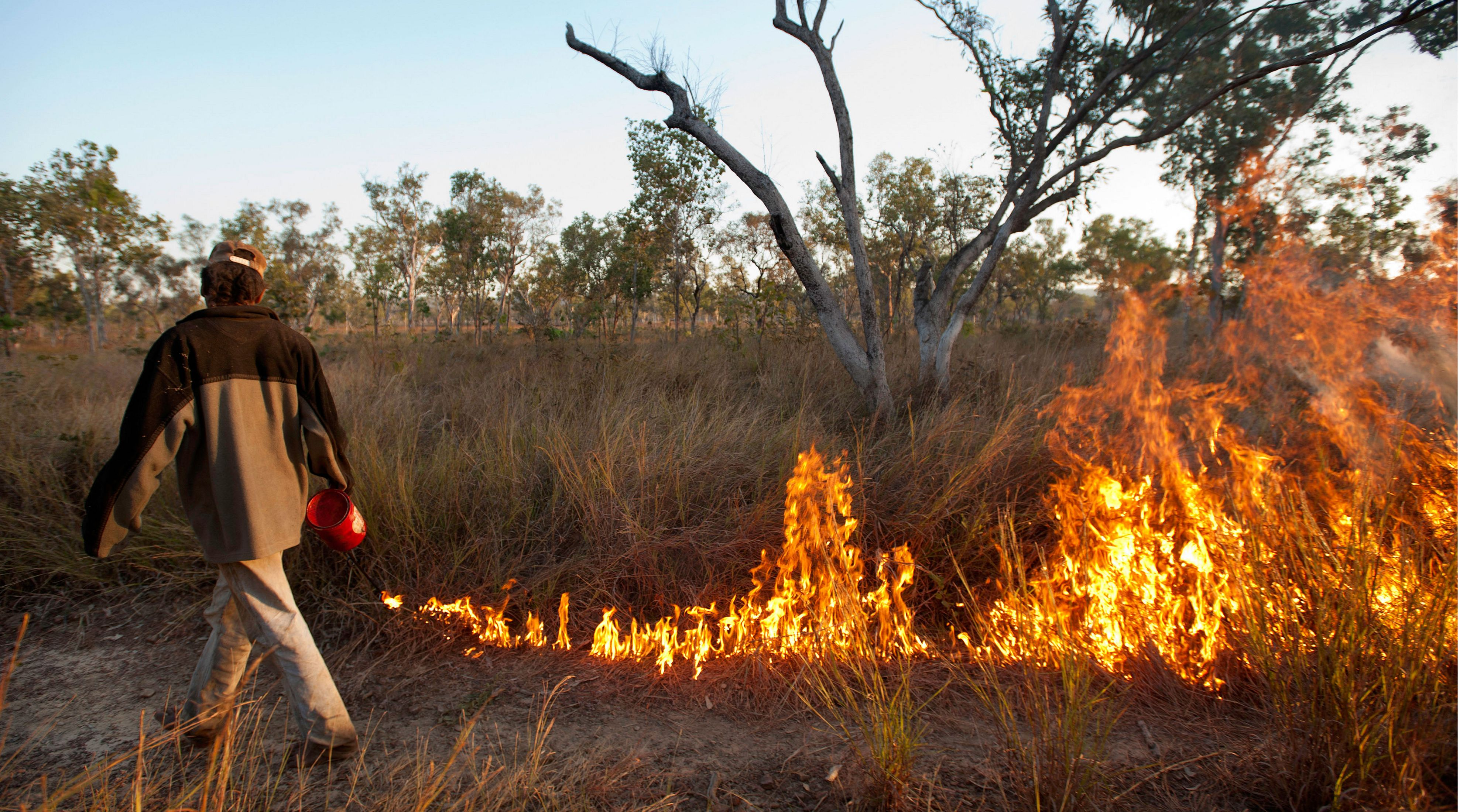 a man tending a controlled burn on a grassland