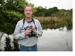 A man holds a camera and stands near a lake.