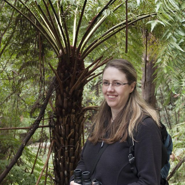 a woman with binoculars stands in front of a palm tree.