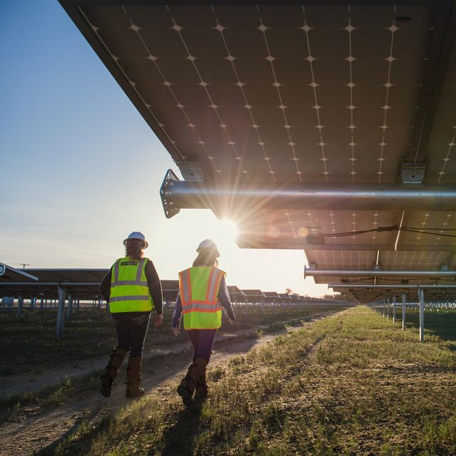 Two people walking next to a solar array