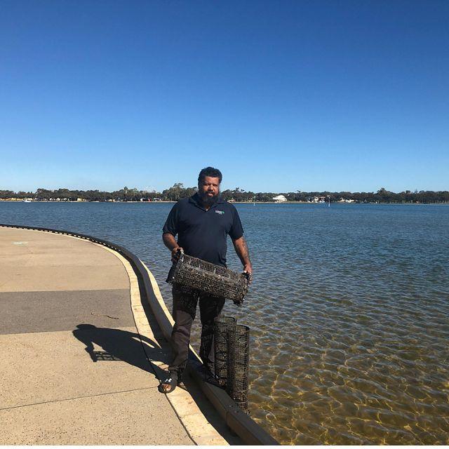 Man holding mussel baskets near estuary