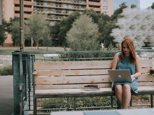 woman sitting with a laptop outside on a bench