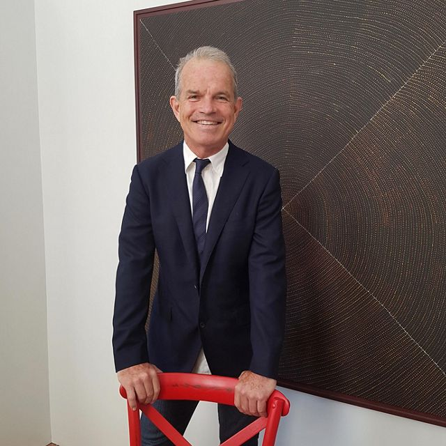 man in a suit leaning on a red chair