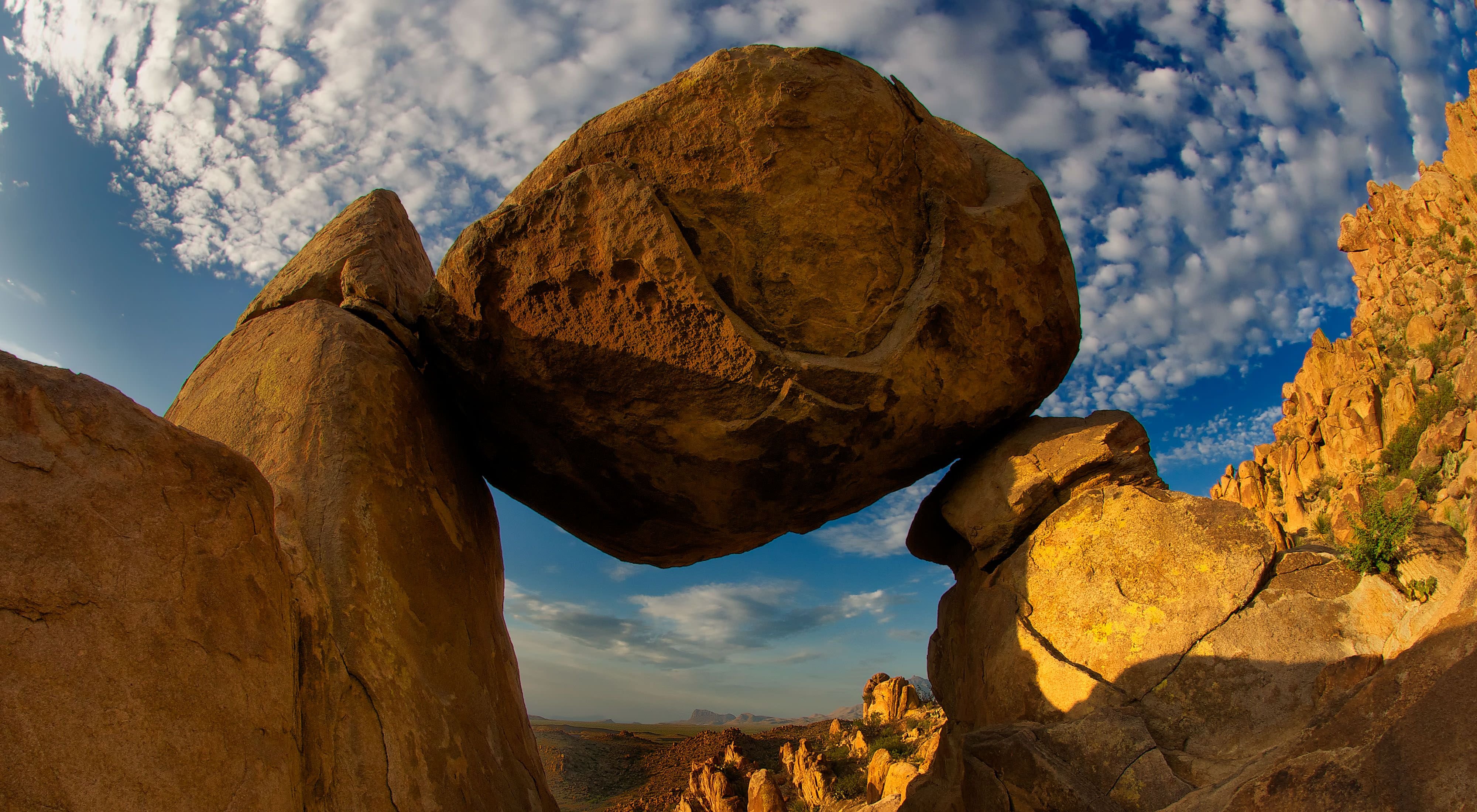 A huge reddish brown boulder balanced above the ground between two other rocks.