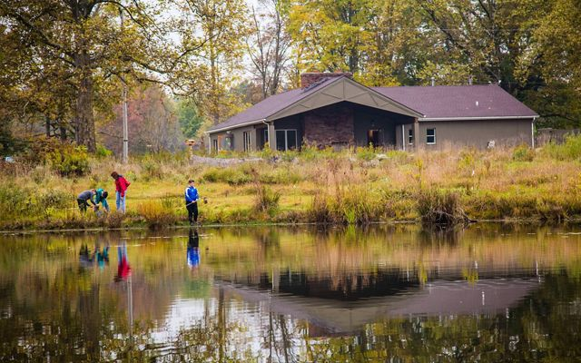 Looking across a pond, four children fishing along the bank, and the nature center building in the background, during the summer.