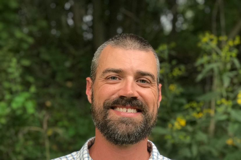 Candid headshot of Allegheny Highlands Program Director Blair Smyth. A smiling bearded man wearing a checked shirt poses outdoors in front of a stand of trees.