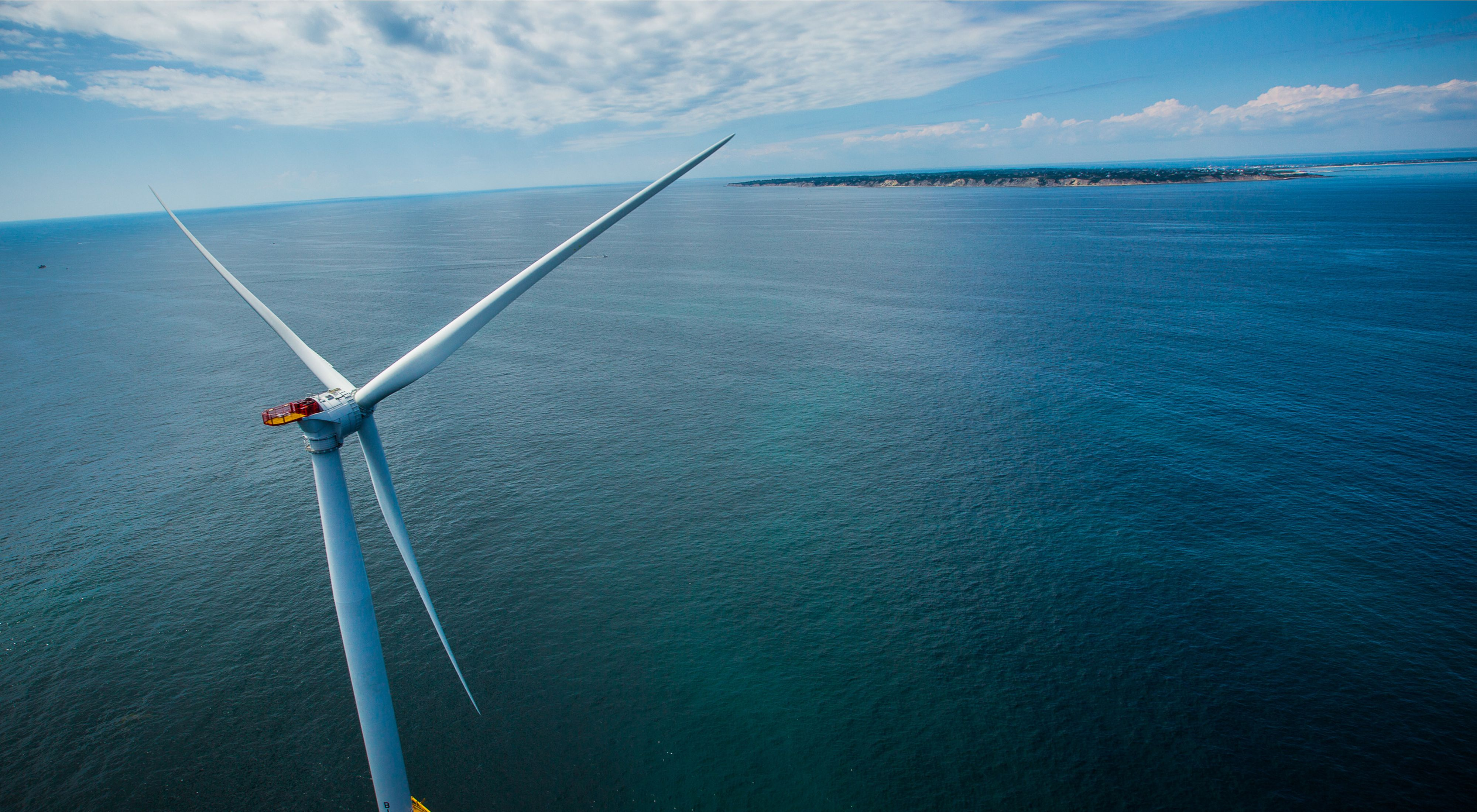 Aerial view of a white wind turbine rising from the ocean, with a small island in the distance.
