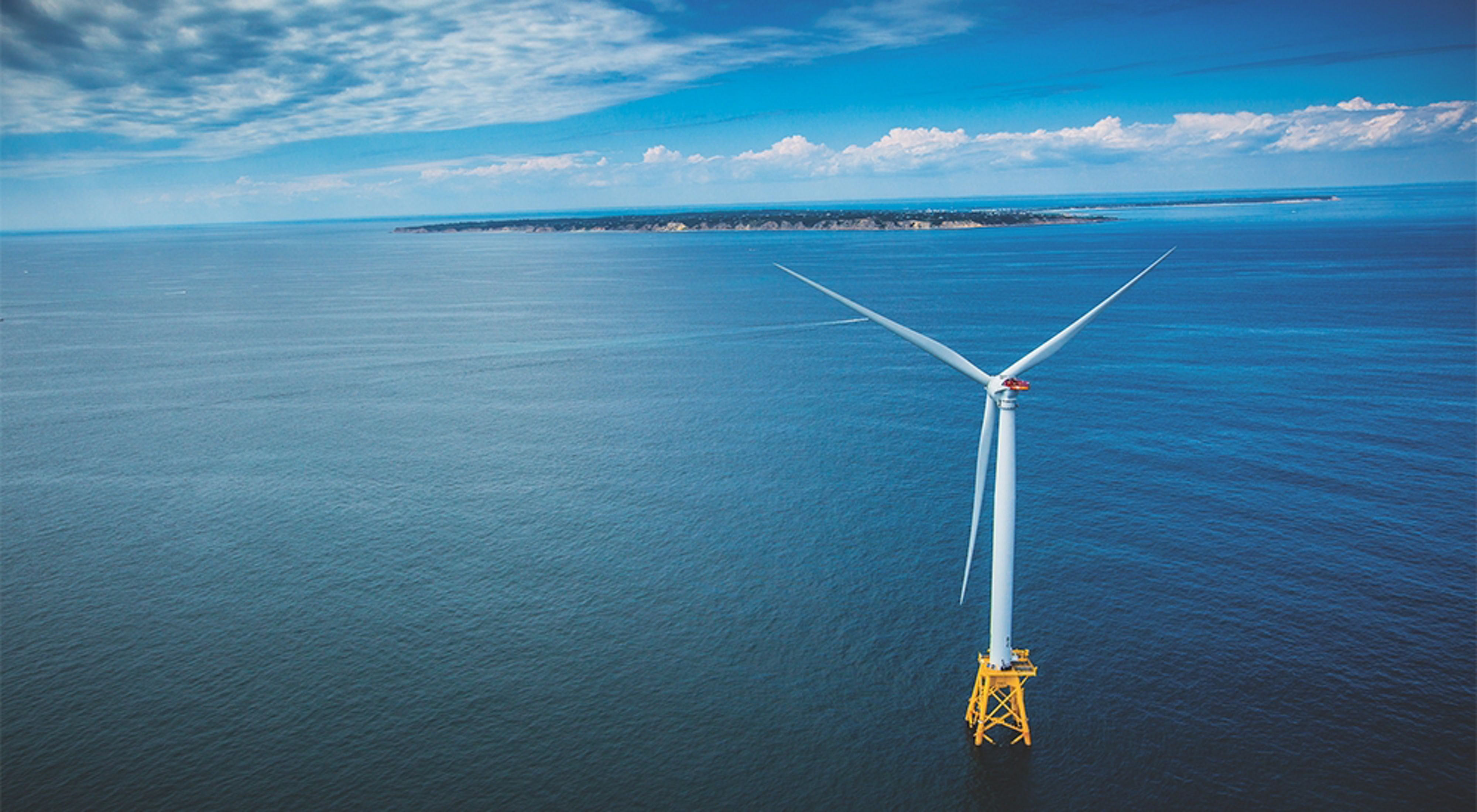 An aerial view of a wind turbine in the ocean with the coast of Block Island and Rhode Island in the background.