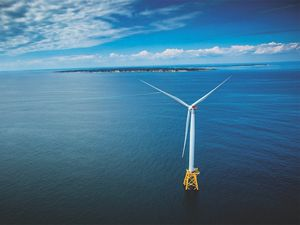 An aerial view of a wind turbine in the ocean, with the coast of Block Island and Rhode Island in the background.