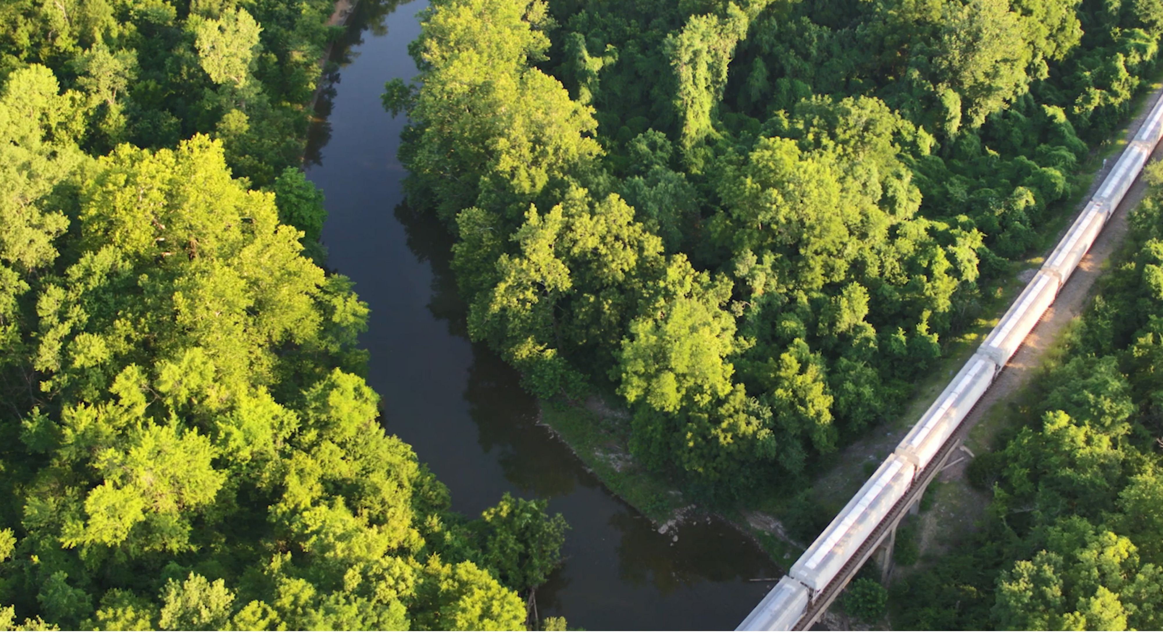 Aerial view train crossing Blue River among trees