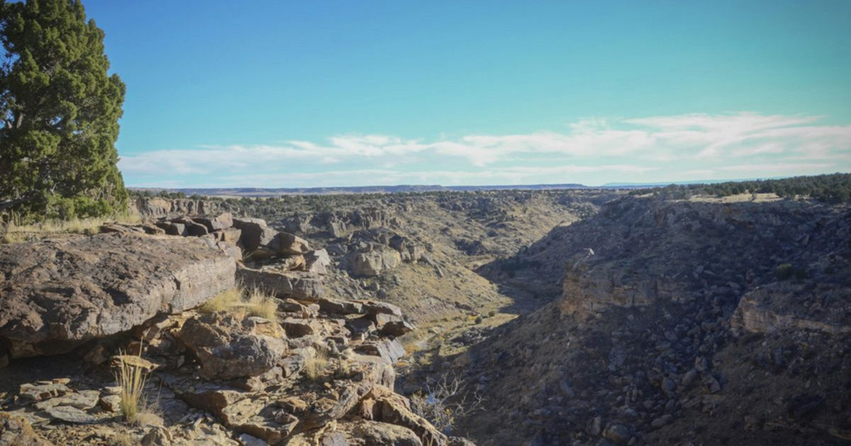 A view of a rocky canyon from the top of a flat mesa, w