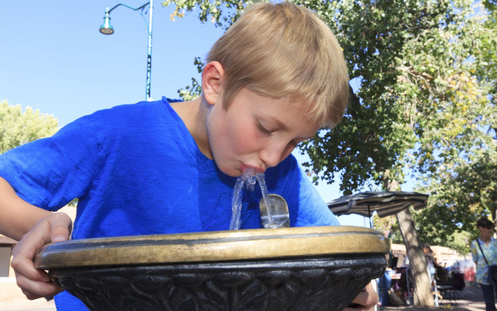 A boy drinks water from a fountain