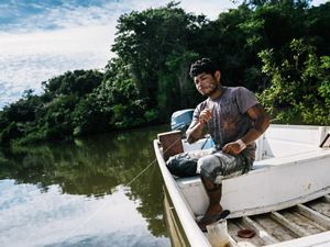 A man holds a fishing line in a boat on a river