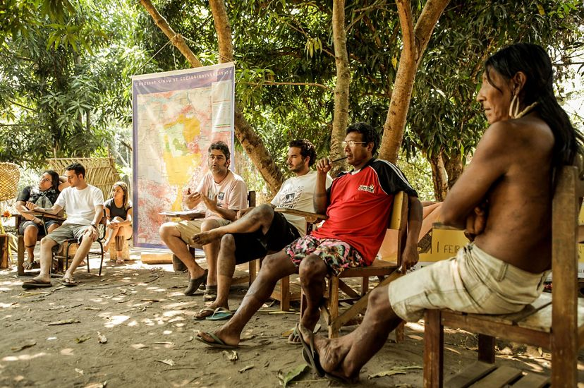 Indigenous men sit in a circle and talk about land management under the shade of trees in Brazil's amazon.