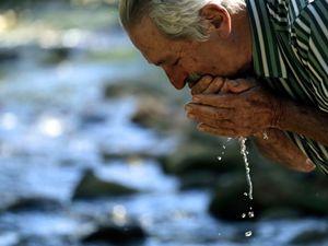 Proprietário rural lava o rosto com água em beira de rio