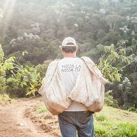 Funcionário do ITPA, organização parceira no distrito de Lídice, em Rio Claro-RJ, carregando mudas de árvores para a restauração de áreas degradadas.