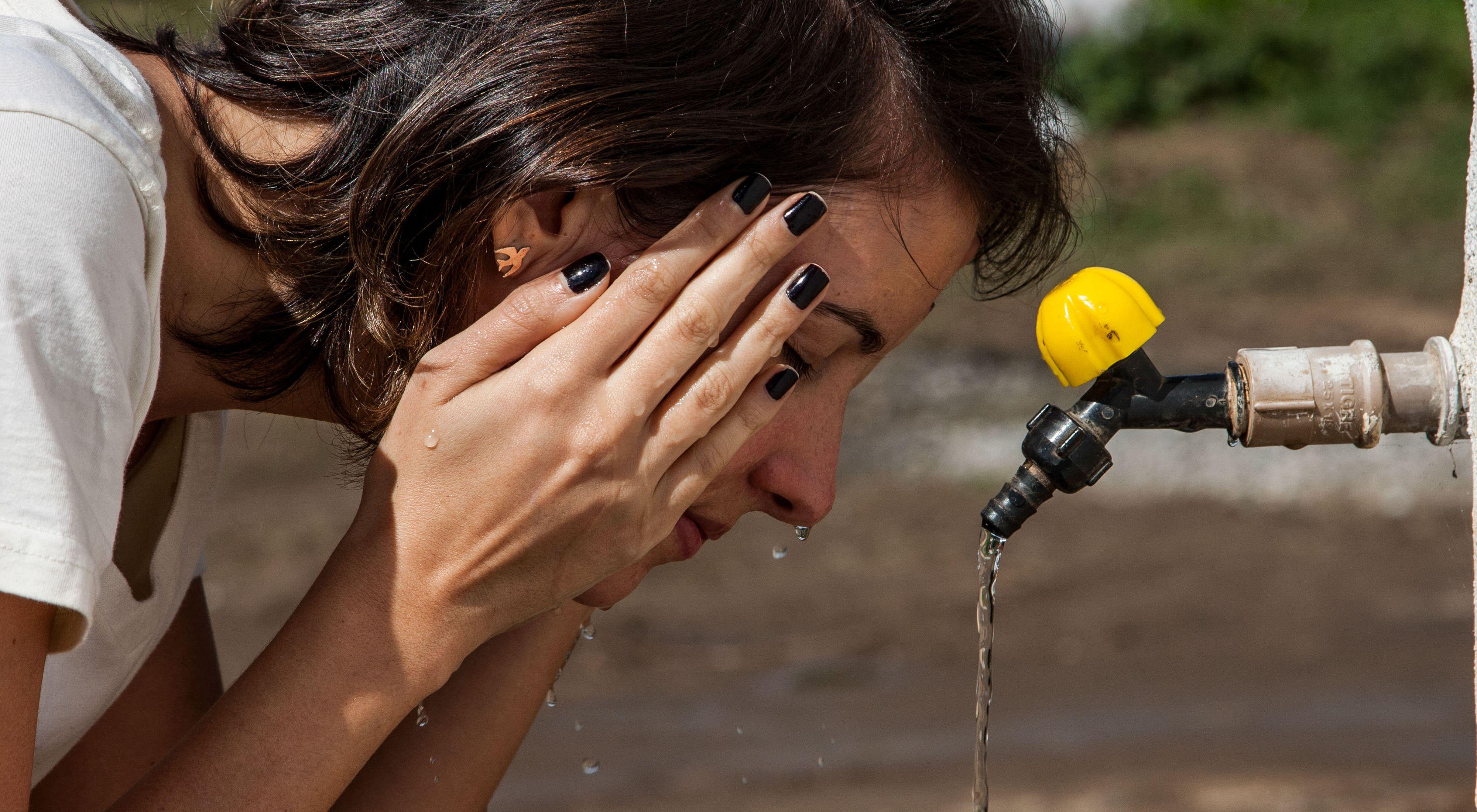 Juliana Bustamante, Assistente Executiva  Gerente de Projetos do ITPA, usa água limpa para lavar as mãos e o rosto, no Brasil.