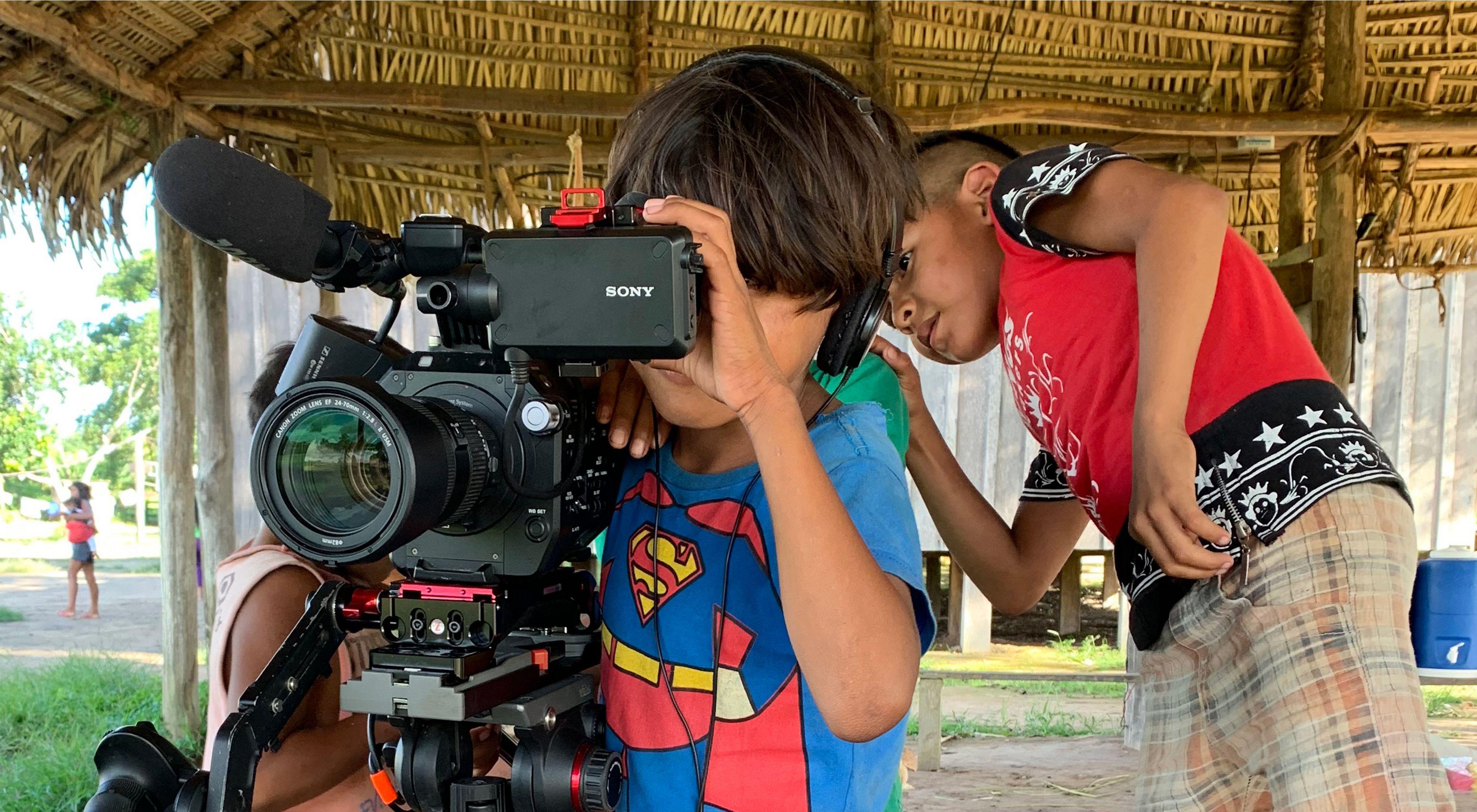 Crianças indígenas do povo Parakanã brincando com a câmera durante as filmagens de uma série sobre artesanato do povo Parakanã.