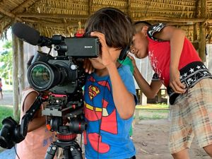 Crianças indígenas bricando com câmera de vídeo.