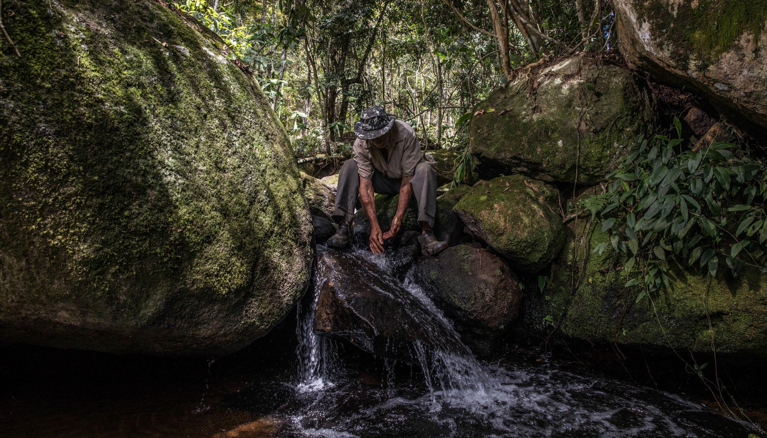 Agricultor lavando as mãos em corrego em sua propriedade