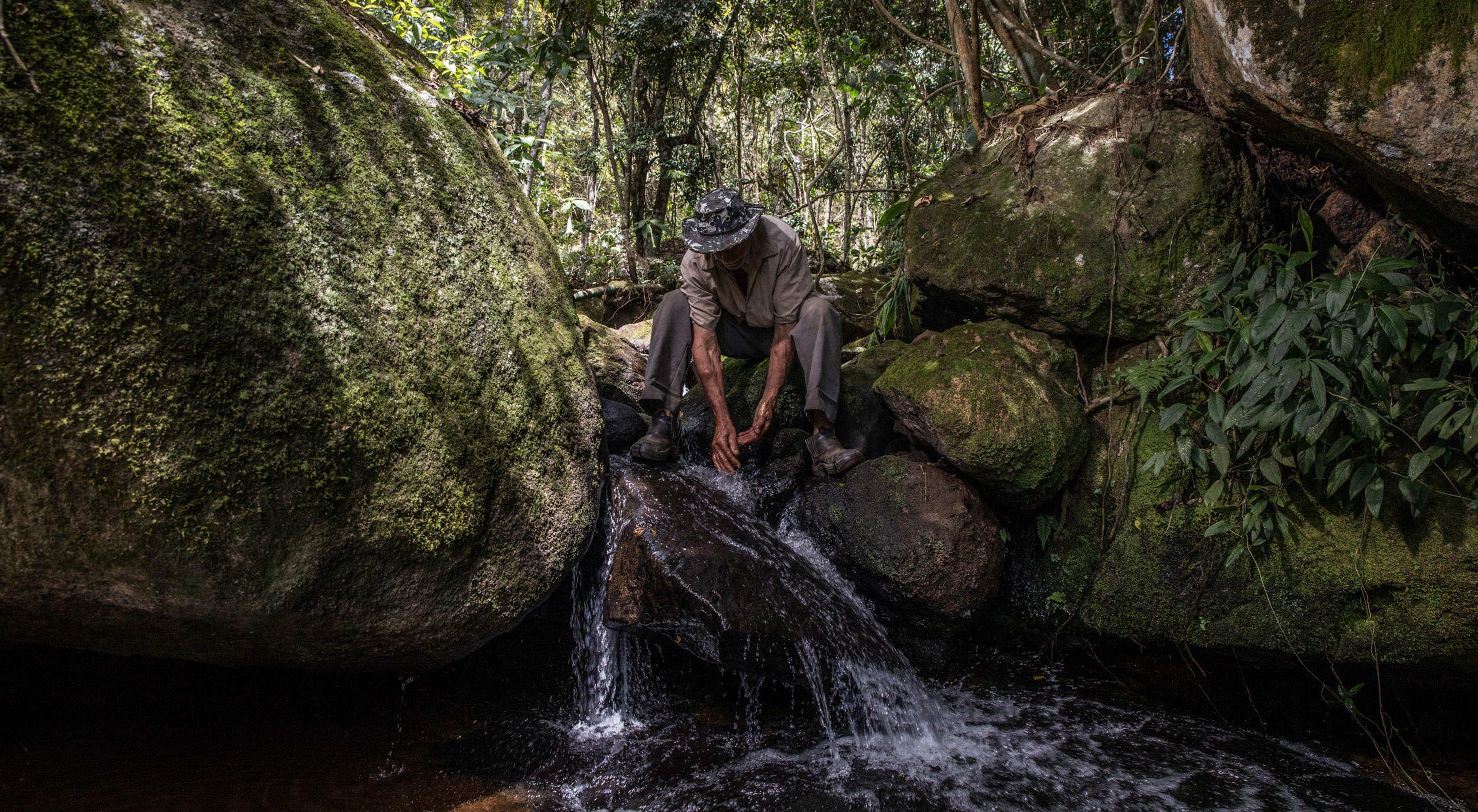 Itamar da Silva lavando as mãos em córrego que ele ajuda a preservar por meio do Pagamento por Serviços Ambientais, em sua propriedade rural em Afonso Cláudio-ES