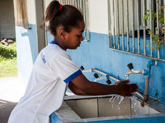 Aluna da escola municipal Rio das Pedras em Rio Claro - RJ lava suas mãos em um tanque.