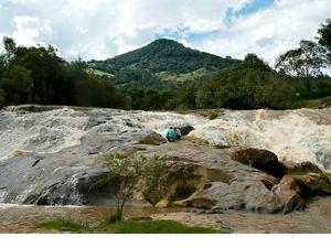Dois pesquisadores examinam água em rio.