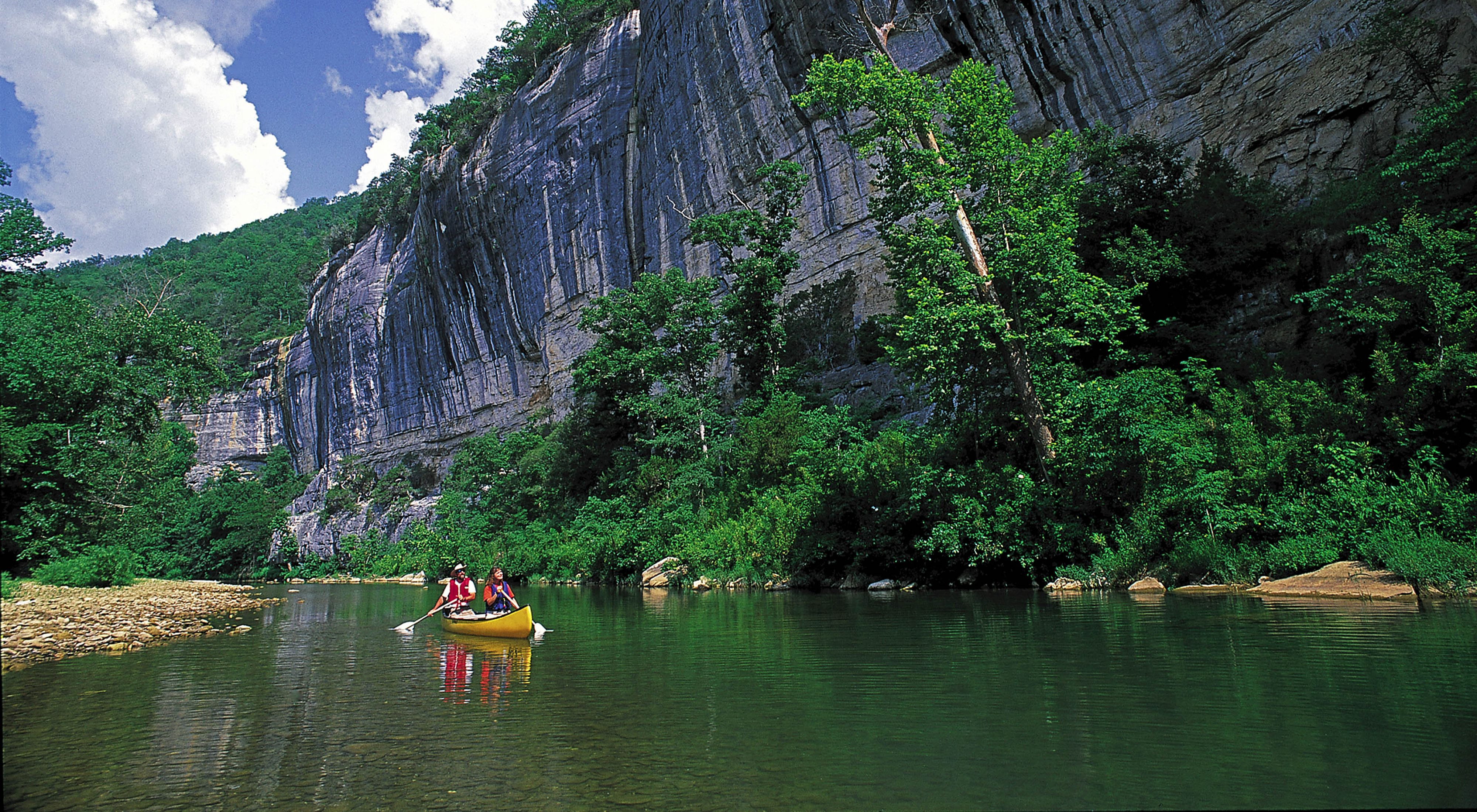 Two people canoeing on the Buffalo River with rocky cliffs along one bank.
