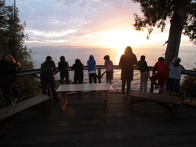 behind view of young people looking from a deck out towards a sunset