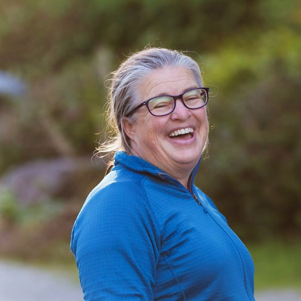 a woman in glasses laughing outside